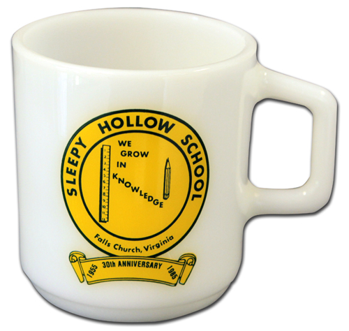 Photograph of a white coffee mug with a yellow seal that reads Sleepy Hollow School, Falls Church, Virginia. We Grow in Knowledge.